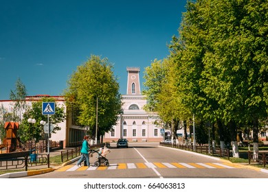 Chachersk, Belarus - May 14, 2017: Woman With A Stroller Crosses The Road On A Pedestrian Crossing.  Old City Hall In Sunny Summer Day On Background. Town Hall In Chechersk