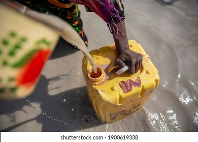 Chad woman are taking dirty water for a drink and use for daily life - Shutterstock ID 1900619338