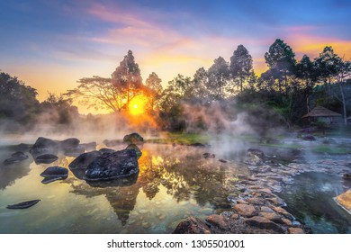 Chae Son National Park, Hot springs over rocky terrain with misty and morning sunrise rays of sun through branches of tree, Lampang Province, Thailand.