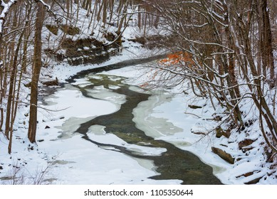 The Chagrin River cuts a narrow channel through ice and snow below the falls in Chagrin Falls, Ohio