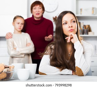 Chagrined young woman having conflict with little daughter and mother