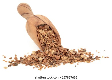 Chai herb tea in an olive wood scoop over white background.