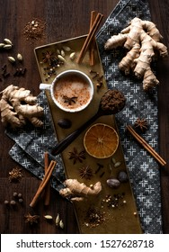 chai tea spices flat lay, chai tea latte with ginger root, cinnamon sticks, cardamom pods, star anise, whole nutmeg, peppercorns, whole cloves on a golden tray and grey patterned cloth napkin on table