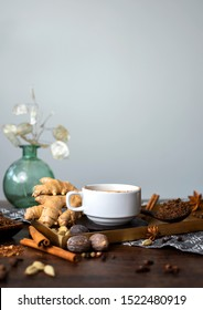 chai tea spices, chai tea latte with ginger root, cinnamon, cardamom pods, star anise, whole nutmeg, peppercorns, whole cloves on golden tray, grey cloth napkin on wooden table, copyspace, copy space
