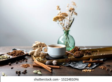 chai tea spices, chai tea latte with ginger root, cinnamon sticks, cardamom pods, star anise, whole nutmeg, peppercorns, whole cloves on a golden tray and grey patterned cloth napkin on table