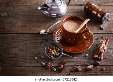 Chai tea and spices over rustic wooden background with copy space