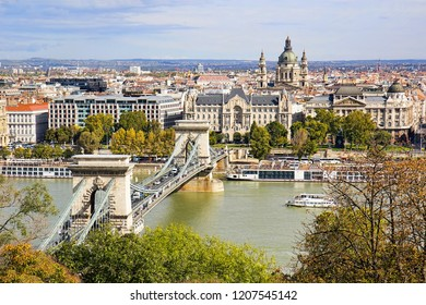Chain Bridge or Szechenyi Bridge across Danube river in Budapest, Hungary, with old buildings and dome of St Stephen's Basilica or Szent Istvan Bazilika, in autumn.