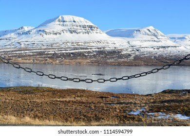 A chain fence with snowy mountains in the background