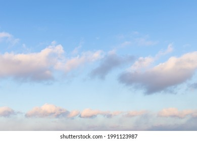 chain of fluffy clouds in blue sunset sky in spring evening