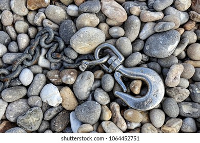 Chain and hook on pebble beach