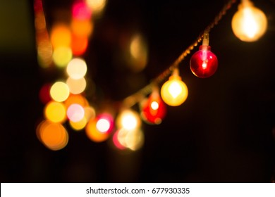 Chain of lights in various colors at a small garden party with red and yellow bulbs in the foreground and unfocused and blured ones in the background