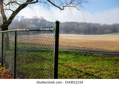 Chain link fence beside a foggy field, Holston River Park, Knoxville, Tennessee, USA