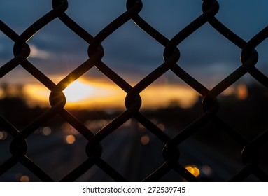 Chain link fence with depth of field, out of focus sunset. Sunset with amazing sunset background. Industrial sunset.
