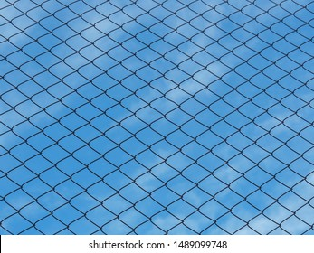 Chain link fence or Mesh fence or iron fence on a blue sky with clouds used as a background