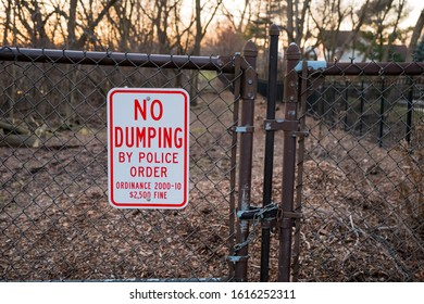 """Chain link fence and metal warning """"No Dumping"""" sign at the cost of penalty. Fenced off due to being a likely area for illegal garbage dumping into lake and river area. Vandalism and polluting"""