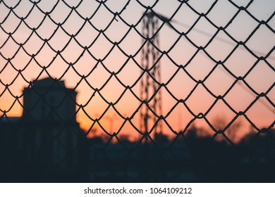 Chain link fence on an evening sunset with depth of field, out of focus sunset. Industrial sunset