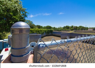 chain link fence surrounding a retention pond
