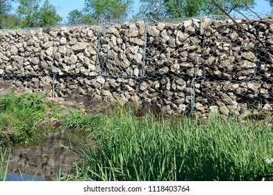 Chain link wire mesh fence creates a cage for rocks and are used to reduce water flow and control erosion.