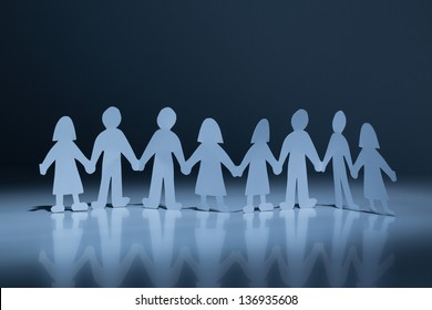 Chain of paper cut people in spotlight against a dark background