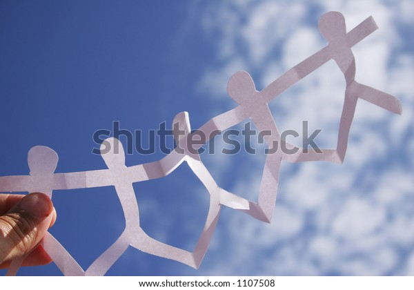 Chain of paper people against the sky