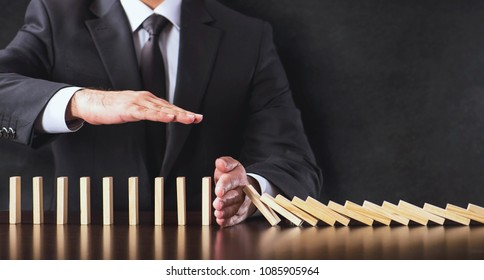 Chain Reaction In Business Concept, Businessman Intervening  Dominos Continuous Toppling and Protecting Assets