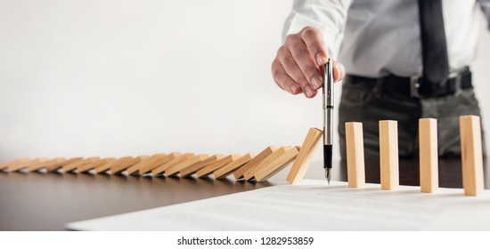 Chain Reaction In Business Concept, Businessman Intervening Chain Dominoes Toppling By Signing A Contract