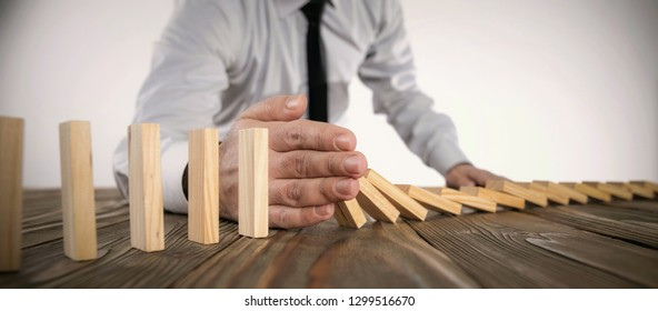 Chain Reaction In Business Concept, Businessman Intervening Dominoes Toppling