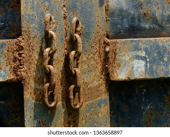 the chain rusts on a dark blue metal plate.