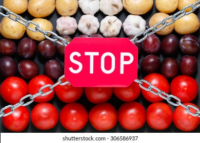 Chain and a 'stop' sign on a vegetables background, in context of sanctions and extermination of food in Russia