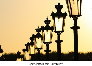a chain of street lamps in Paris in the late sunlight