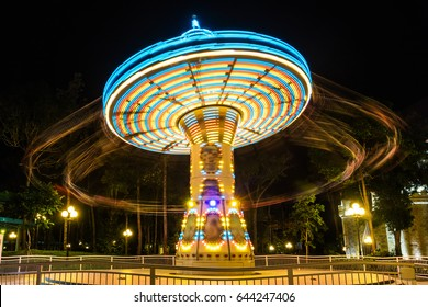 chain swing carousel ride in amusement park at night