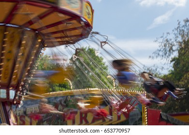 Chain swing carousel ride at a carnival with motion blur during sunset