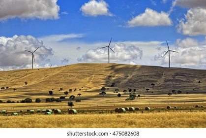 chain of tall win turbines on top of hills in Sough Australia. Rural region with cultivated farms and haystacks providing grounds for renewable energy