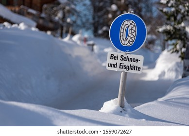 Chain traffic sign: Bei Schnee und Eisglätte. Blue warning information:  Snow chain obligation, Winter time and winter services. Snow covered road, trees. Styria, Austria - Shutterstock ID 1559072627