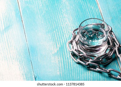 chain wraps a glass with a liquor, wooden background