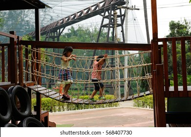 CHAINAT, THAILAND- 19: Unidentified child crossed wooden bridge in playground on February 19, 2015 in Chainat, Thailand.The playground is in Chainat Bird Park.