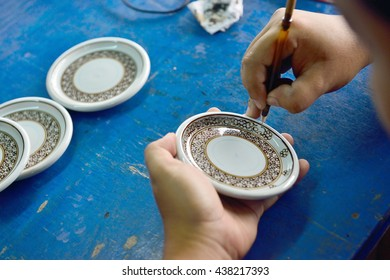 CHAINAT, THAILAND - OCTOBER 17, 2014 : Thai people working process paint Ceramic Benjarong is traditional Thai five basic colors style pottery at workshop on October 17, 2014 in Chainat, Thailand.