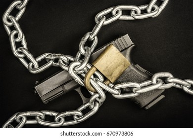 A chained up handgun kept safe from those who are a danger to society.