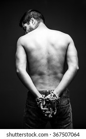Chained man hands, angry and shirtless. Slave back.