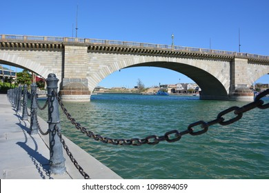 The chained walkway pointing to the London Bridge in Lake Havasu Arizona on a warm spring day.  An interesting perspective showing the bridge in the distance.