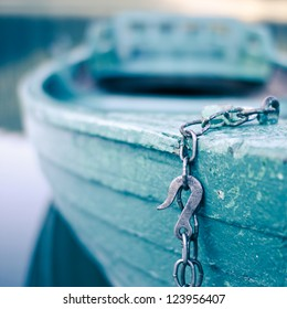 Chained wooden boat is waiting for sunday passengers. Focus is on the hook and the boat in background is blurry.