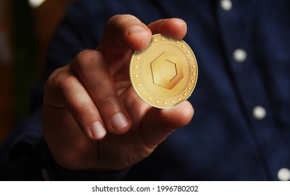 Chainlink link cryptocurrency symbol golden coin in hand abstract concept.