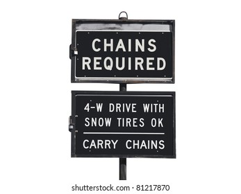 Chains or snow tires required sign with mountain backdrop.