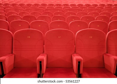 Chair #7. Empty cinema auditorium with lines of red chairs.