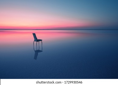 Chair among smooth water of lake at the sunset. The concept of solitude and unity with nature. A chair stands in the water of the Salt Lake Ace. Anatolia, Turkey