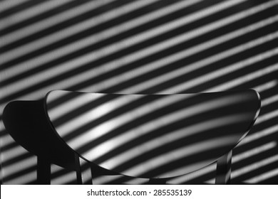 Chair backrest under the stripy shadow in black and white