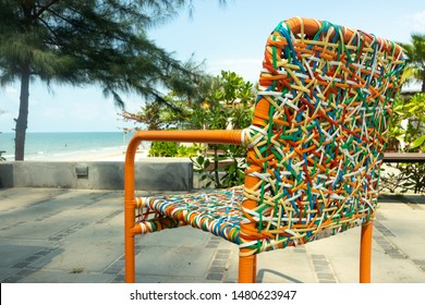 Chair backrest of variety colors of rattan lines that are alternately woven into mesh style in the garden with beach view