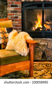 Chair by a cozy fireplace with a crackling fire. Gas insert with a glass screen. Style is rustic elegance, lodge, arts and crafts, upscale cabin.