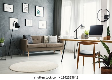 Chair at desk with desktop computer in grey open space interior with brown sofa under posters. Real photo