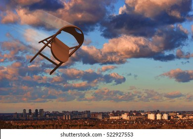 Chair flying in the sky. Brown - orange chair motion on background of urban landscape, blue sky, pyellow pink clowds.
